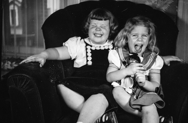 Two little girls laughing on a  sofa